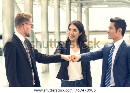 Businessman businesswoman making fist bump on stock photo royalty young businessman and businesswoman making a fist bump on modern building background business people m4hsunfo