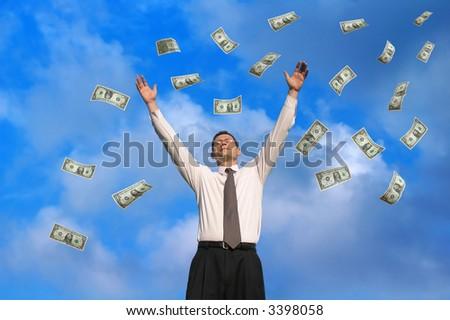 Young businessman catching raining dollars - stock photo