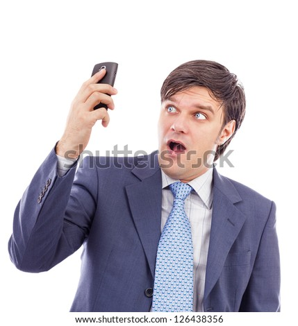 Young businessman holding a mobile phone and looking surprised against white