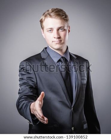 Young Businessman In A Suit Holds Out His Hand For A Handshake - stock photo