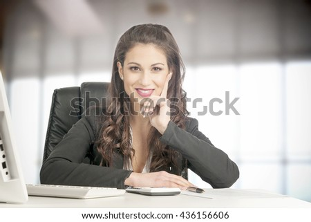 Young Businesswoman Sitting At Desk in her Office - stock photo