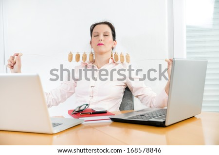young businesswoman with neck pain sitting at office desk and uses and uses mas-sager