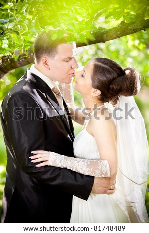 Young caucasian just married couple kissing and hugging in park