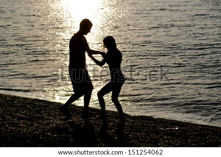 young couple playfully dancing on a   beach.