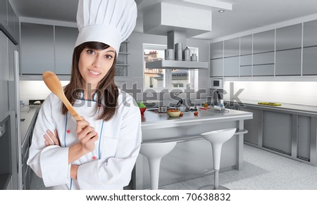 Young female chef holding a wooden spoon - stock photo