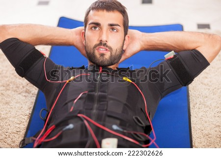 young fit man exercise on  electro muscular stimulation machine - stock photo