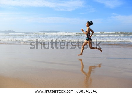 young fitness woman wear swimsuit running on beach