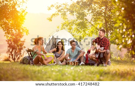 young friends have good time on camping trip, relaxing vacation with fun - stock photo