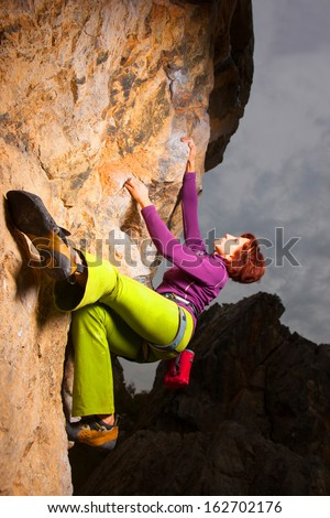 Young girl climbing on a limestone wall  - stock photo