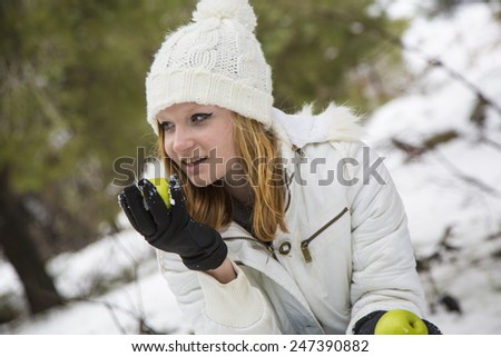 Young girl in white hat holding apples in winter forest - stock photo