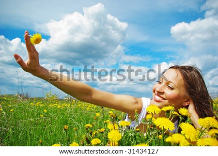 Young girl relaxing on a meadow, holding dandelion - stock photo