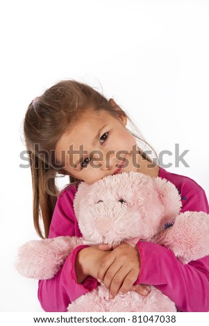 Young girl with pink dress hug teddy in studio portrait - stock photo