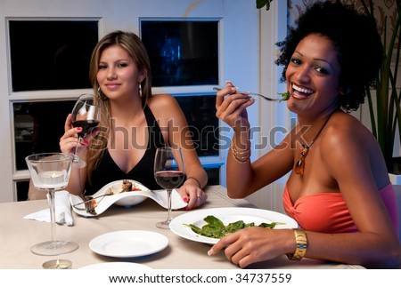 2 Young girls having dinner in a restaurant. - stock photo