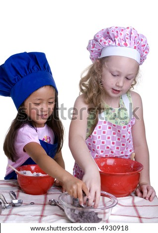 2 young girls having fun in the kitchen making a mess....I mean making something special..... Education, learning, cooking, childhood - stock photo