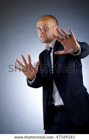 Young, handsome businessman. Hiding behind his hands