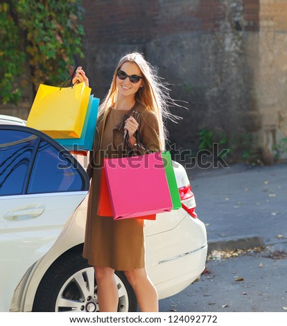 Young happy woman with shopping bags near the car outdoors - stock photo