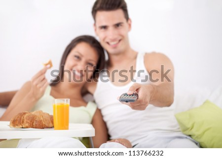 Young love couple having breakfast and watching TV in bed - stock photo