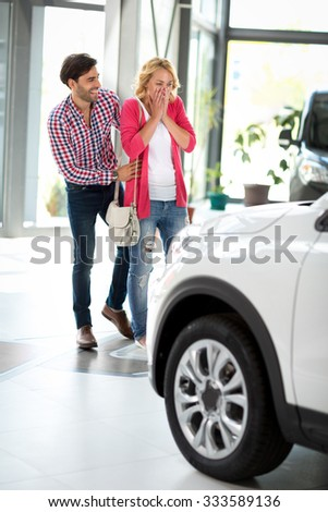 Young man about to surprise girlfriend with new car in  car dealership saloon - stock photo
