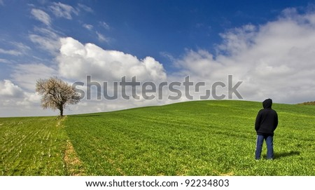 Young man and old tree in meadow - stock photo