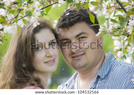 Young man and the woman against a blossoming apple-tree - stock photo