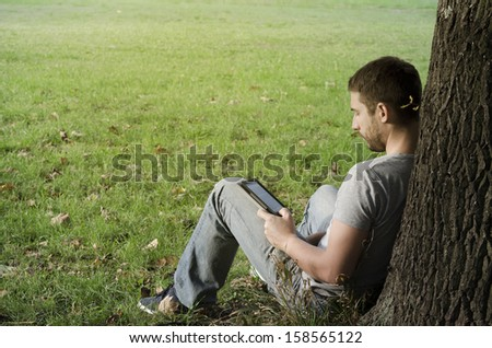 Young man reading e-book under the tree - stock photo