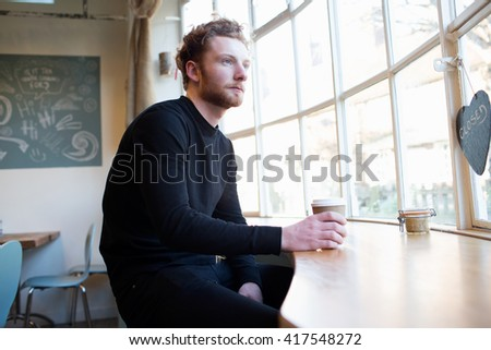 Young Man Sitting In Window Of Coffee Shop - stock photo