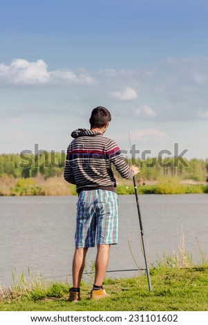 young man with a fishing rod on the river bank  - stock photo