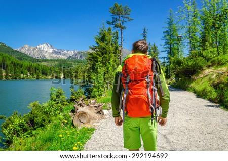Young man with an orange backpack doing trekking along a mountain lake, Strbske Pleso, High Tatras, Slovakia - stock photo