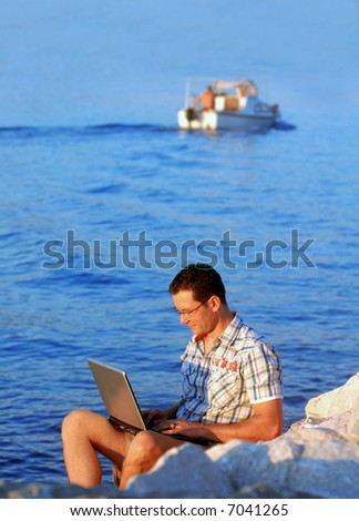 Young man with laptop at the beach - stock photo