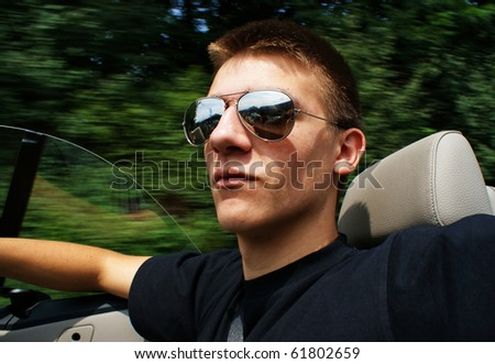 Young man with sunglasses traveling in convertible car.