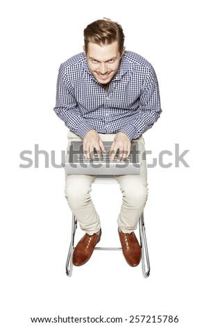 Young man working on a computer on his knees. - stock photo