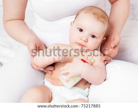 young mother and her six months old baby with a bottle of milk - stock photo