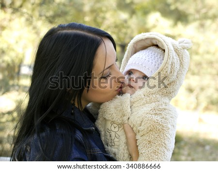 young mother kisses her baby outdoors - stock photo