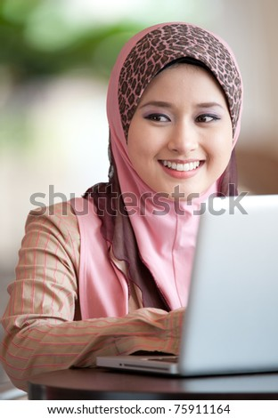 young muslim woman in head scarf using laptop in cafe
