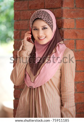young muslim woman in head scarf using phone - stock photo
