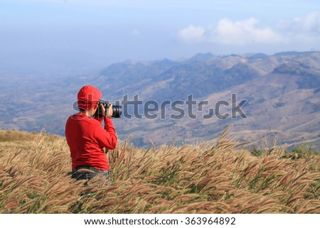young photographer is holding the camera in a pasture on the hill.