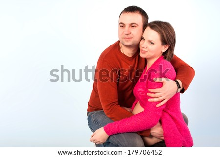 Young pregnant woman and man. Pregnant family. Studio shot - stock photo