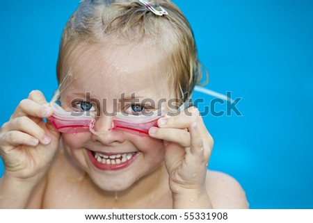 Young pretty girl in swimming-pool holding her swimming glasses. In background is blue water visible. - stock photo
