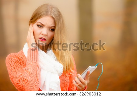 young sad or annoyed woman student girl with headphones listening music mp3 or learning language outdoors in autumn park - stock photo