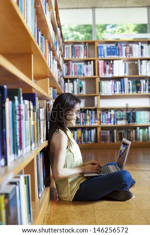 Young smiling student using her laptop in a library - stock photo