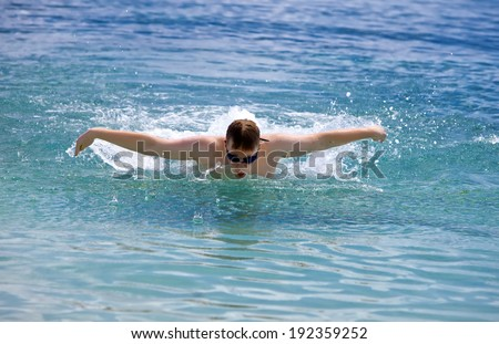 young sporting man swims in the sea butterfly stroke style - stock photo