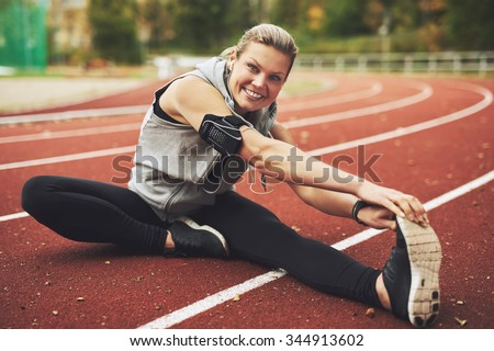 Young sportswoman sitting and stretching on track field while listening to music, looking at camera. - stock photo