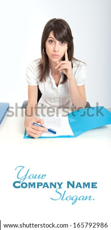Young woman at a desk examining a document with a pen in her hand  - stock photo