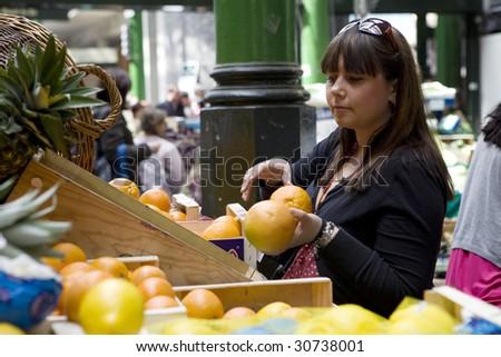 Young woman buying orange  at Borough market - stock photo