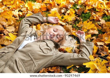 young woman dreams in autumn leaves - stock photo