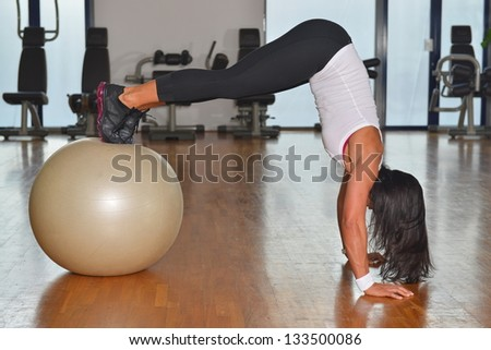 Young woman exercising fitness ball workout - stock photo