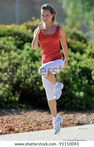 young woman exercising in the park in summer