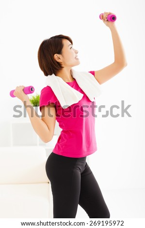 young woman exercising with dumbbells in living room - stock photo