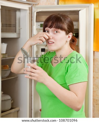 young woman holding her nose because of bad smell from food near refrigerator  at home