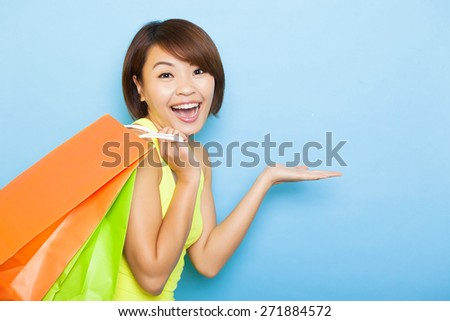 young  woman holding shopping bags before blue background - stock photo